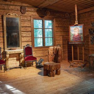 Sisäkuva Alpo Jaakolan kodista Loimaalla patsaspuistossa, taulu maalaustelineellä, kaksi tuolia, peili