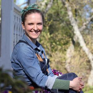 Nainen sinisessä paidassa istuu portailla ja hymyilee kameraan. Takana vihreitä puita.
