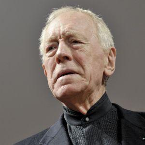 Max von Sydow, en man i svart kostym och grått hår.