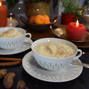 Två vita tekoppar av risporslin. I kopparna finns det äggtoddy, en varm drink som är gjord på uppvispat ägg, socker, varm mjölk och kryddor. Bredvid kopparna finns kanelstänger, muskotnötter, tända ljus och mandariner.