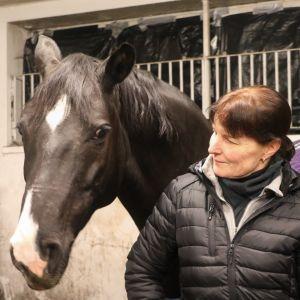 Kikko Kalliokoski med sin häst i ett stall.