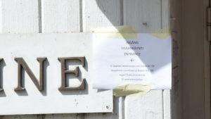 en papperslapp fasttejpad vid ingången till Motel Marine. Det står att ingången är flyttad och att baren öppnar klockan 9, men att det inte serveras någon frukost.