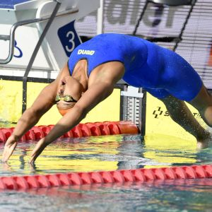 Mimosa Jallow dyker i vattnet för ett ryggsimslopp