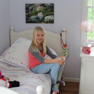 Lia Hartwall sitter på sängen i sitt rum i USA