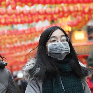 Två kvinnor går på en gata i London dekorerad med kinesiska dekorationer. Båda bär munskydd.