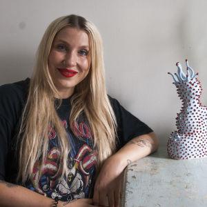 Meikkitaiteilija Piia Hiltunen istuu pöydän vieressä musta t-paita päällään.