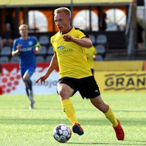 KuPS-spelaren Ilmari Niskanen avancerar med bollen.