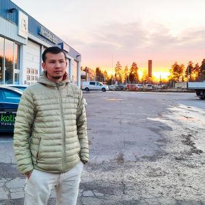 Man står utanför bilverkstad i solnedgång.