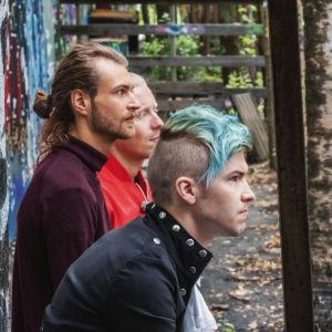 Tre män sitter på en bänk och lyssnar uppmärksamt, omgärdade av träd, i bakgrunden graffitimålning.
