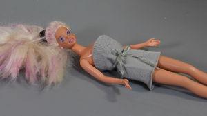 En Barbiedocka ligger på ett bord. Hon har på sig en fodralklänning gjord av en skaftet från en gammal strumpa