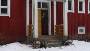 Jon LIndström vid ytterdörren till en gammal skola, numera hem och kursgård. Vinter