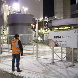 En strejkvakt i orange väst och svart mössa står utanför en pappersfabrik.