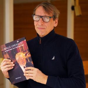 En man står och håller i en bok. På boken finns en bild av en annan man.