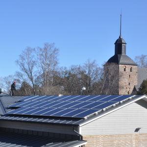 Solpaneler på butikstak - i bakgrunden syns Korpo kyrka.