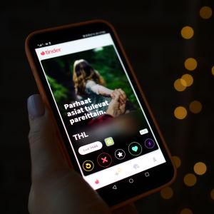 En hand som håller i en mobiltelefon. Mobilskärmen är upplåst med dejtingappen Tinder aktiverad, och på den syns Institutet för hälsa och välfärds reklambild för unga om att ta coronavaccin.