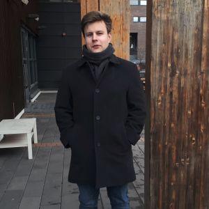 En man iklädd svart jacka står bredvid en mörkare träpelare.