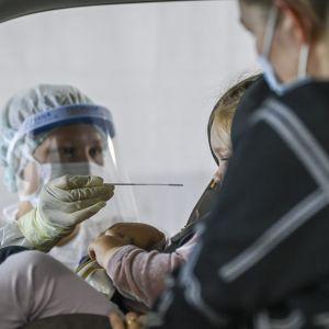 En sjukskötare i skyddsutrustning testar ett barn för coronaviruset. Barnet sitter i en bil i en bilstol, bredvid henne sitter en vuxen kvinna i munskydd.