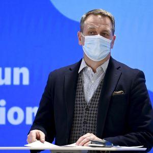 Medelålders man i kostym och munskydd står vänd mot kameran med blått och ljusblått i bakgrunden. Helsingfors borgmästare Jan Vapaavuori den 18 februari 2021.