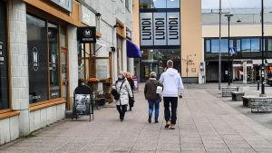 Personer som promenerar i stad, en kvinna bär munskydd.