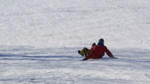 Kvinna åker ner för borgbacken i Borgå med pulka, med ett barn i famnen