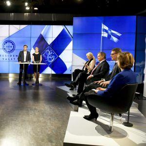 Bild på de åtta kandidaterna i tv-studion.