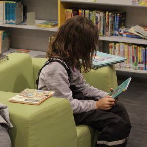 Två stycken barn sitter och läser i ett bibliotek.