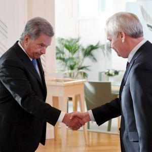 Sauli Niinistö och Antti Rinne skakar hand.