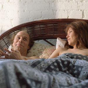 Vesa-Vierikon näyttelemä ohjaaja ja Outi Mäenpään esittämä näyttelijä makaavat sängyllä ja pitävät toisiaan kädestä kiinni.