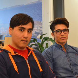 17-åringarna Ezzat Najafi och Masaud Alizada sitter på en soffa i deras boende, i bakgrunden korridor, krukväxter och matbord.