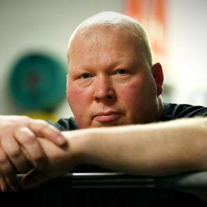 Styrkelyftaren Ove Lehto sitter och lutar sig mot en skivstång i gymmet.