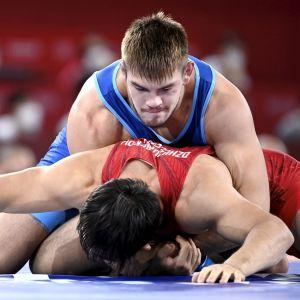 Arvi Savolainen håller ner sin motståndare Uzur Dzhuzupbekov mot mattan.