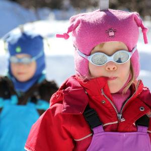 Två barn i treårsålder, ute i snön med polariserande solglasögan.