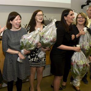 Borgmästare Jan Vapaavuori, fullmäktigeordförande Tuuli Kousa, biträdande borgmästare Anni Sinnemäki, Pia Pakarinen, Nasima Razmyar och Sanna Vesikansa får blommor i fullmäktigesalen.