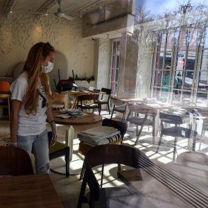 En kvinna med långt hår och ansiktsskydd står i ett tomt kafé.