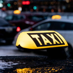 En gul taxi-skylt på ett biltak, i bakgrunden fler taxibilar.