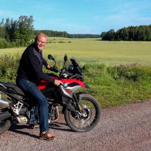 En man sitter på en motorcykel framför en åker.