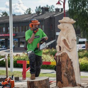 Mies tekemässä puuveistosta, moottorisaha kädessä, miettii, käsi leualla, vieressä valmistumassa karhun mallinen puuveistos