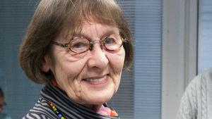 Äldre kvinna med brun page och glasögon ler mot kameran.