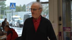 Äldre mansperson promenerar genom sjukhusaula.