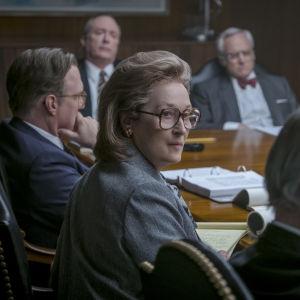 Närbild på Katharine Graham (Meryl Streep) i ett konferensrum fyllt av män.