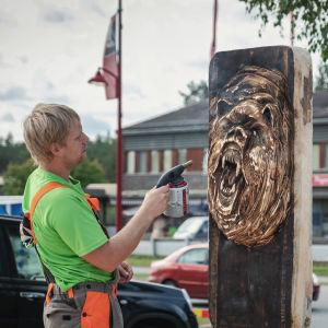 Mies polttaa kaasupolttimella puuveistossa, karhun kuva