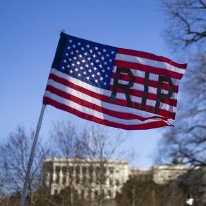 USA:s flagga med texten RIP. I bakgrunden syns Kapitoliums kupol.