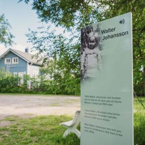 """QR-koodilla varustettu kyltti, jossa ruotsinkielistä tekstiä ja otsikko """"Walter Johansson"""" Paraisten Vanhalla Malmilla opastamassa matkailijoita."""