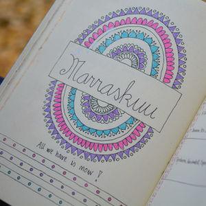 """En kalender där Riikka har ritat in en färgrann Mandala symbol i lila, rosa och turkost. Hon har också skrivit in texten """"All we have is now!"""" med svart penna."""