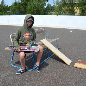 En pojke sitter på en bänk med en skejtboard i famnen.