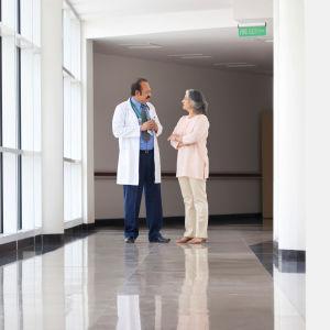 Läkare och patient diskuterar i en sjukhuskorridor.