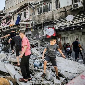 Palestiinalaisia tarkastelemassa tuhottuja taloja.