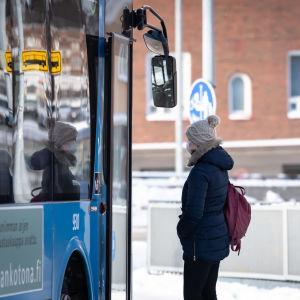 Ihmisiä bussipysäkillä Malmin asemalla.
