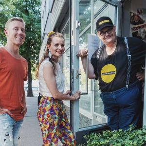 Sami Helle tervehtii Pertin valinta -myymälän ovella Egenlandin juontajia Hannamari Hoikkalaa ja Nicke Aldénia, kesäinen katunäkymä taustalla