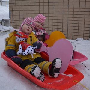 Lilja och Enni Latvakangas, två barn i vinterkläder och rosavitrandiga mössor, sitter i varsin pulka.
